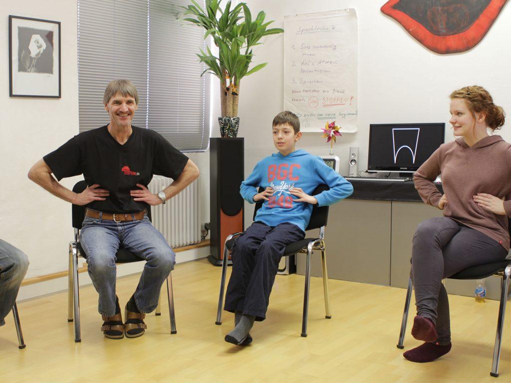 Stottertherapeut Hans Liebelt und weitere Teilnehmer sitzen im Stuhlkreis und wenden eine Atemtechnik an.