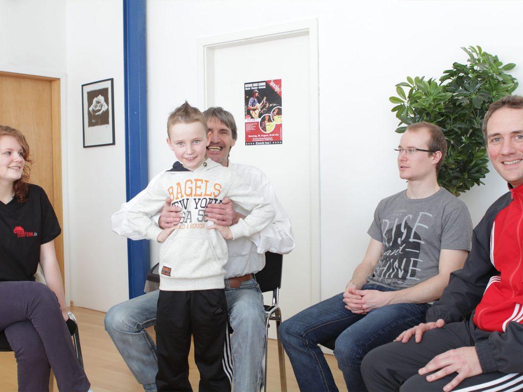 Stottertherapeut Hans Liebelt unterstützt einen jungen Teilnehmer bei der Flankenatmung.