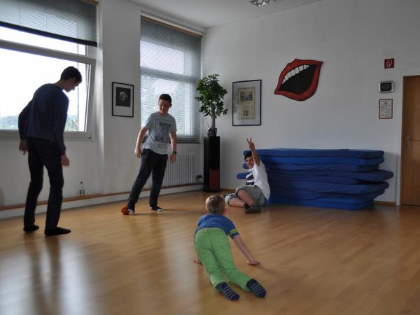 Eine Kindergruppe spielt Fußball in der Pause während der Stottertherapie